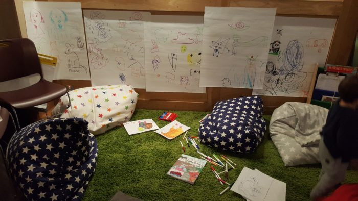 the children's drawing space with colourful pictures on the wall and bean bags scattered over the floor