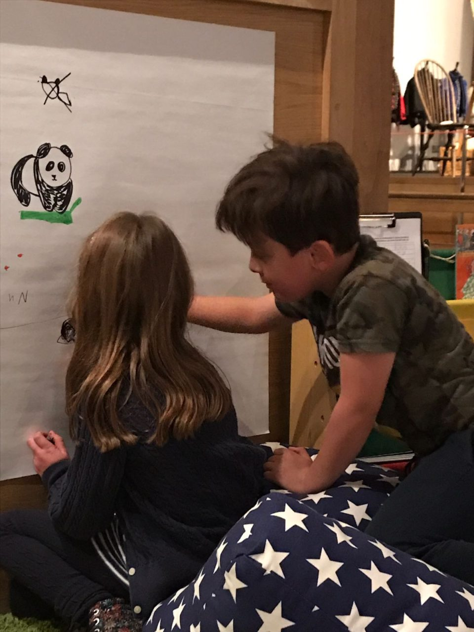 Children drawing pictures on  a board